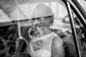 Braut schaut durch die Scheibe im Hochzeitsauto