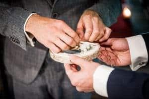 Bräutigam nimmt Ehering vom Baumstamm