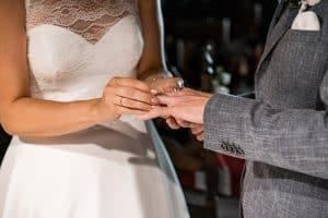 Braut steckt Ring auf den Finger vom Bräutigam