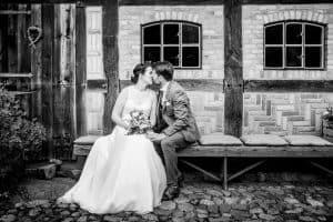 küssendes Brautpaar sitzt auf einer Bank vor einem Fachwerkhaus