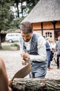 Bräutigam mit sich biegender Säge beim Holz sägen