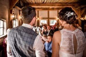 Brqautpaar spriucht zu den Gästen in einer Scheune